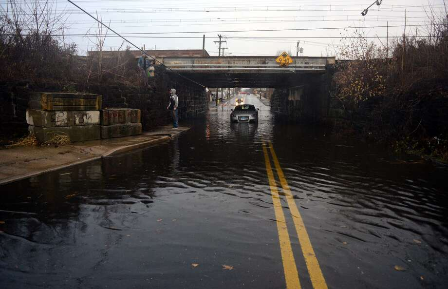 Heavy rains flood an area near a train bridge in Stratford. Photo: Christian Abraham / Hearst Connecticut Media / Connecticut Post