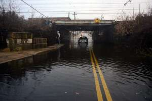 Heavy rains flood an area near a train bridge in Stratford.