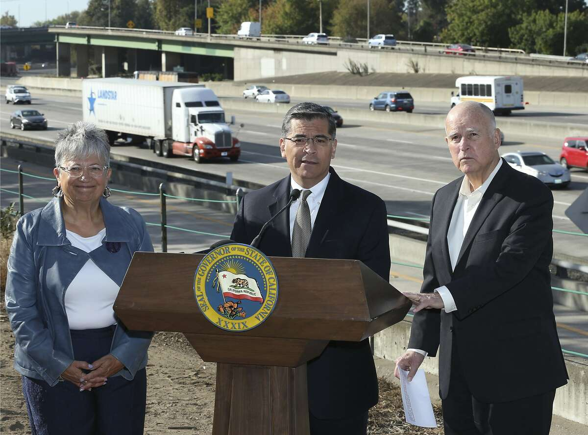 FILE - In this Oct. 26, 2018 file photo, California Attorney General Xavier Becerra, center, discusses a Trump administration plan to freeze vehicle emissions standards during a news conference in Sacramento, Calif. Becerra was joined by California Air Resources Board Chairperson Mary Nichols, and Gov. Jerry Brown. Becerra immediately became perhaps the nation's most influential attorney general when he was named California's top lawyer two years ago. (AP Photo/Rich Pedroncelli, File)