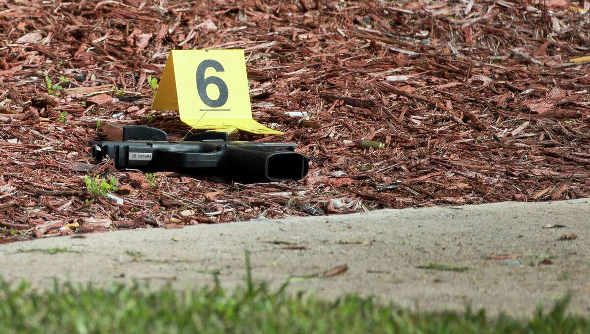 Members of the Houston Forensic Science Center placed an evidence marker next to a gun at the scene of an officer-involved shooting at 11050 Southwest Freeway Service Road Tuesday, Jan. 8, 2019, in Houston.