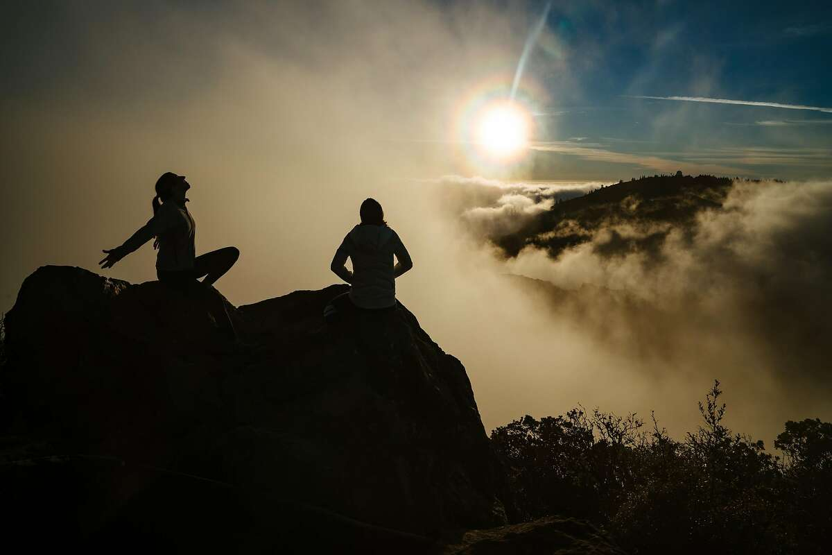 Ashley Meyers and Britt Williams Baker watch as the fog breaks through on the East Peak at Mount Tamalpais State Park in Mill Valley, Calif., on Wednesday, Dec. 19, 2018.