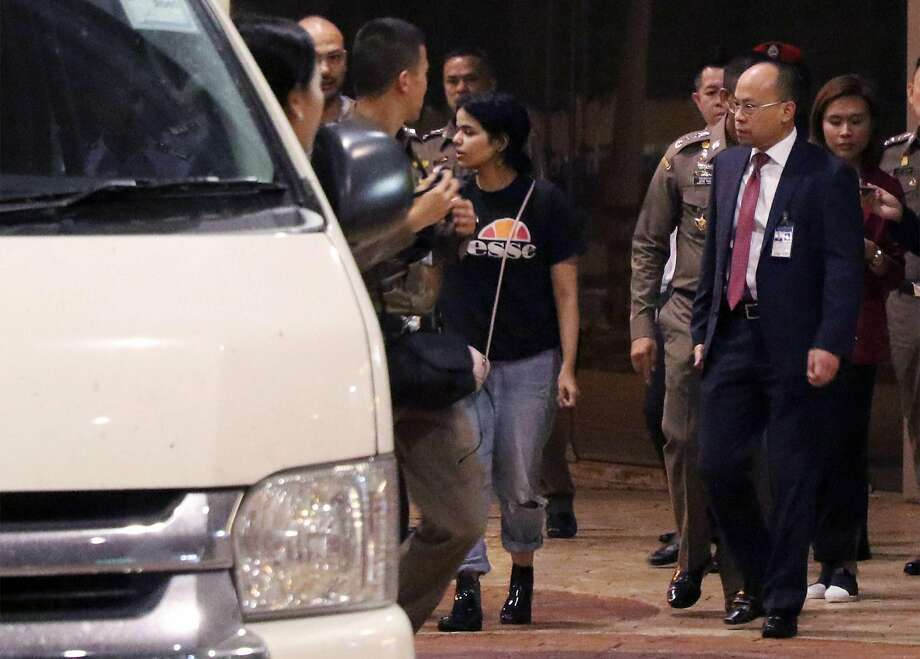 Rahaf Mohammed Alqunun (center) is escorted to a van Monday by a Thai immigration officer and officials of the U.N. High Commissioner for Refugees at Bangkok's international airport. Photo: AFP / Getty Images