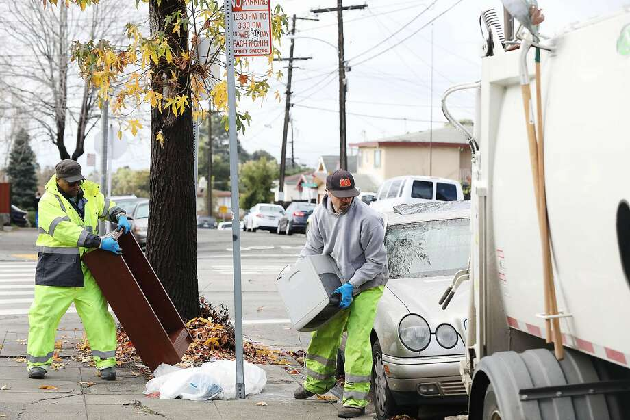City workers Ayinde Osayaba (left) and David Conti carry refuse to the back of a garbage truck. Photo: Lea Suzuki / The Chronicle
