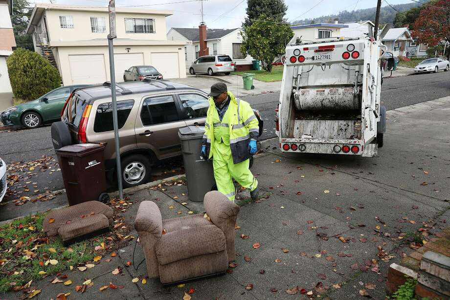 Oakland maintenance worker Ayinde Osayaba prepares to haul away a chair abandoned on the street. Photo: Photos By Lea Suzuki / The Chronicle