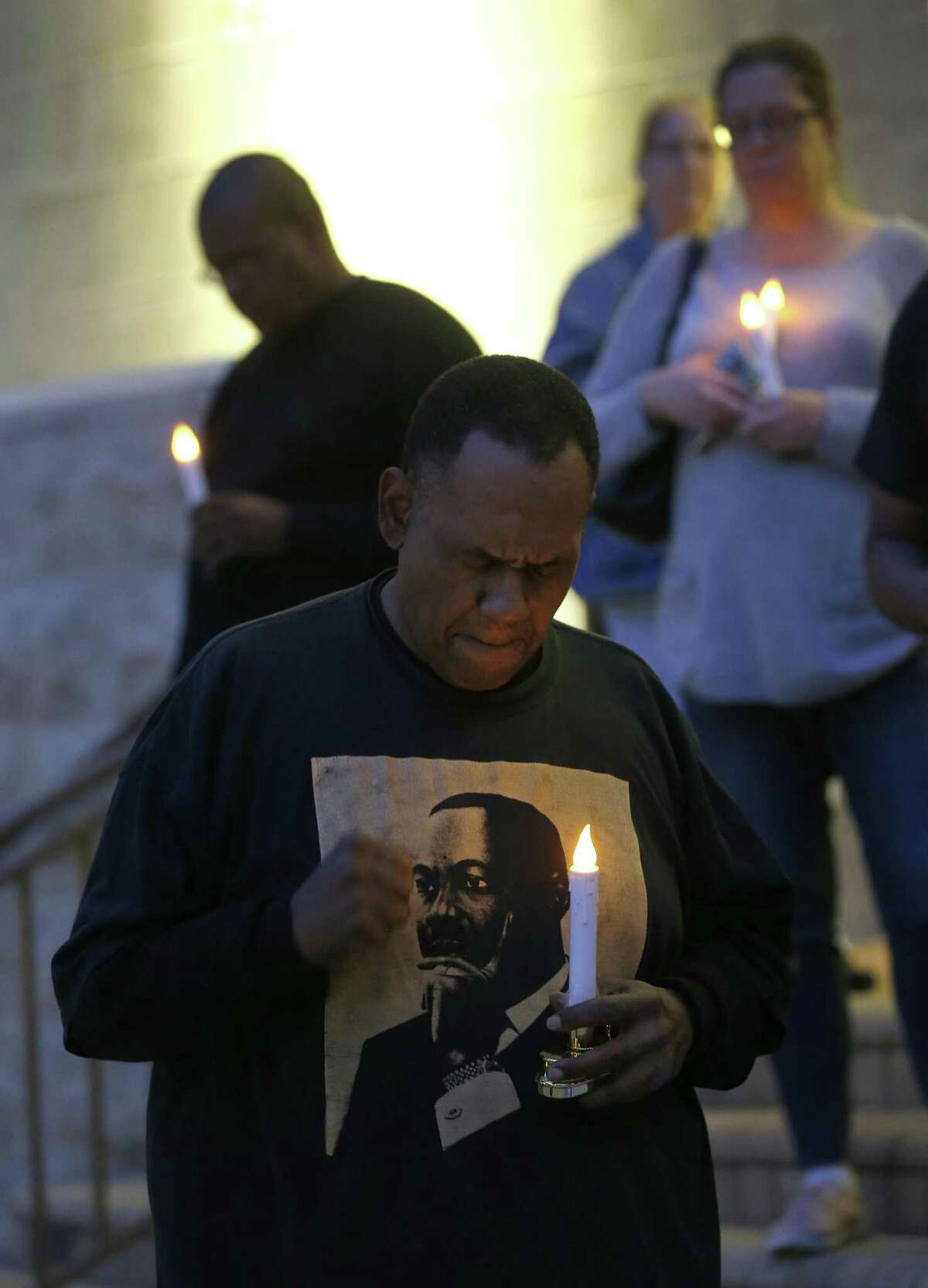Activist Reginald Moore prays during a moment of silence as he and other community members held a candelight vigil on the steps of City Hall, Sunday, Dec. 16, 2018, at Sugar Land Town Square, in Sugar Land, to honor the 95 African-American remains found at Fort Bend ISD construction site earlier this year.