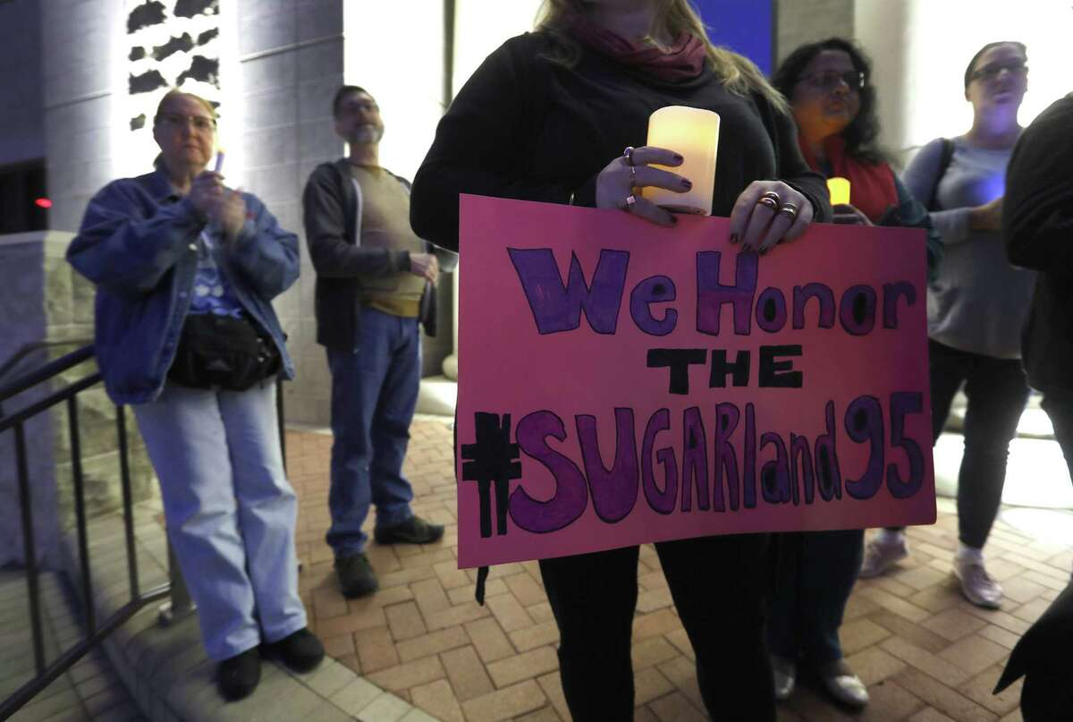 Kathy McDougal holds a sign that reads