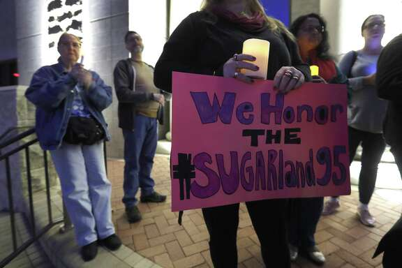 """Kathy McDougal holds a sign that reads """"We Honor the #Sugarland95"""" during a candelight vigil on the steps of City Hall, Sunday, Dec. 16, 2018, at Sugar Land Town Square, in Sugar Land, to honor the 95 African-American remains found at Fort Bend ISD construction site earlier this year."""