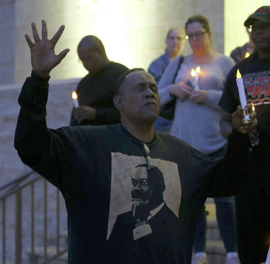 Activist Reginald Moore prays during a moment of silence as he and other community members held a candelight vigil on the steps of City Hall, Sunday, Dec. 16, 2018, at Sugar Land Town Square, in Sugar Land, to honor the 95 African-American remains found at Fort Bend ISD construction site earlier this year. Photo: Karen Warren,  Houston Chronicle / Staff Photographer / © 2018 Houston Chronicle