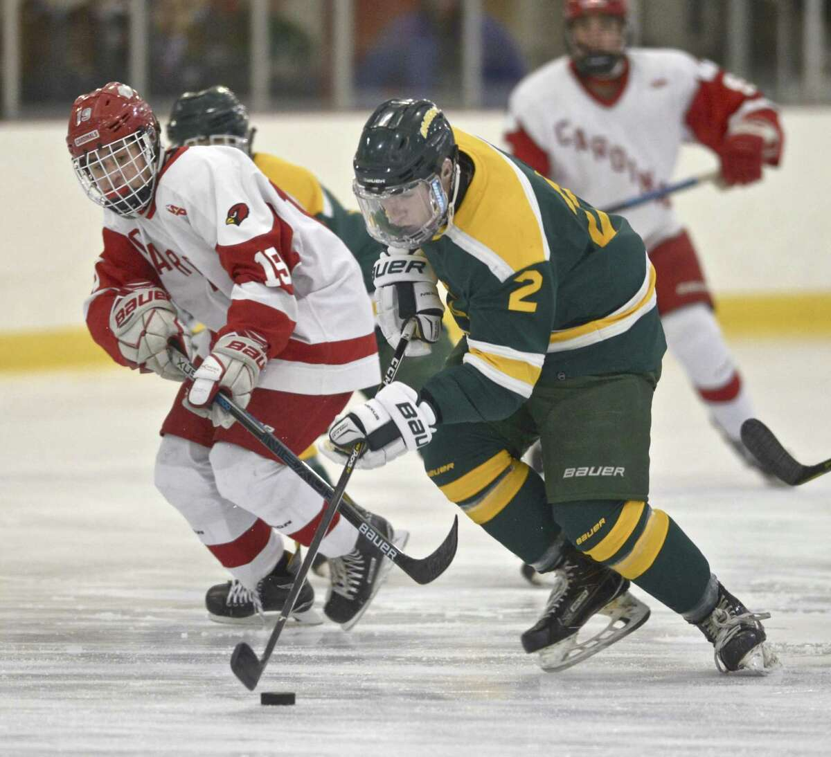Hamden's Michael Gethings (2) moves the puck while under pressure from Greenwich's Julian Ribushofski on Jan 2.