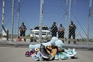 Shoes and a teddy bear, brought by a group of U.S. mayors, are piled up outside a holding facility for immigrant children in Tornillo, Texas, near the Mexican border in June. A group headed by Richard Villasana tries to connect immigrant children with relatives as an alternative to foster care.