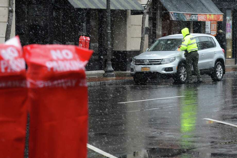 A traffic enforcement officer issues a ticket for a car illegally parked on Bedford Street during a snowstorm in Stamford in March 2018. New rules can make getting a ticket in the city much more expensive. Photo: Michael Cummo / Hearst Connecticut Media / Stamford Advocate