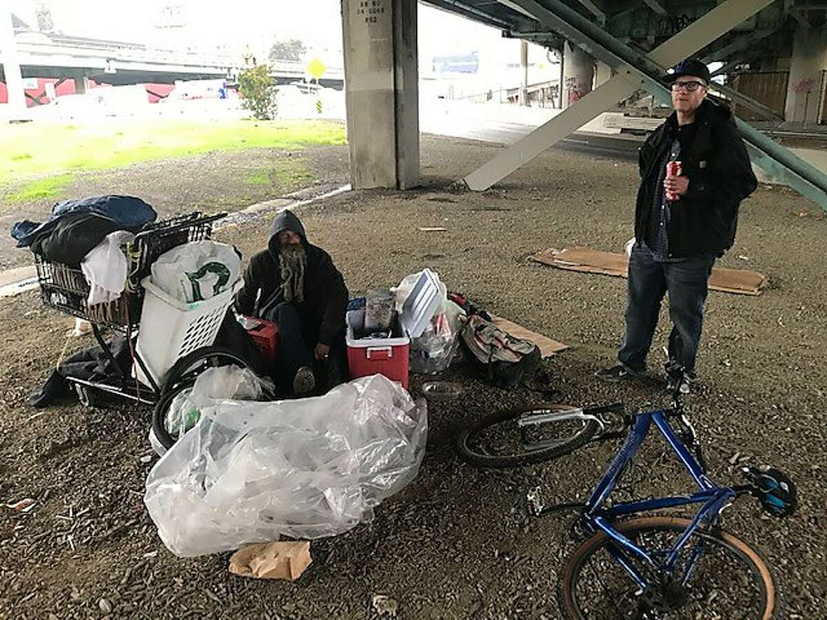 Homeless campers Niev Khabeiry, left, and Brian Martin hope they can move into San Francisco's newest Navigation Center homeless shelter, which is opening in January 2019 across the street from where they sit under the Interstate 80 freeway.