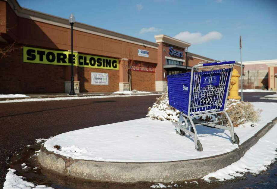 FILE- In this Tuesday, Jan. 1, 2019, file photo, an empty shopping cart sits in the snow outside a Sears store in the Streets of Southglenn mall in Littleton, Colo. Sears is getting another reprieve from liquidation after its chairman and largest shareholder revised his bid to save the iconic brand. The Hoffman Estates, Illinois-based retailer says it has accepted Eddie Lampert's bid through an affiliate of his ESL hedge fund that could keep 425 stores open and save tens of thousands of workers, according to a hearing on Tuesday, Jan. 8, 2019, at the bankruptcy court in White Plains, N.Y. (AP Photo/David Zalubowski, File) Photo: David Zalubowski / Copyright 2018 The Associated Press. All rights reserved.