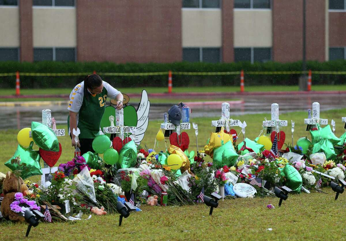 Sierra Dean, 16, writes on a cross while visiting the memorial for the mass shooting victims at Santa Fe High School Wednesday, May 23, 2018, in Santa Fe, Texas. Vaughan, seven other students, and two staff members were killed by alleged shooter Dimitrios Pagourtzis, 17, last Friday. ( Godofredo A. Vasquez / Houston Chronicle )
