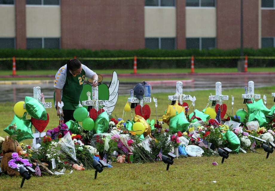 Sierra Dean, 16, writes on a cross while visiting the memorial for the mass shooting victims at Santa Fe High School Wednesday, May 23, 2018, in Santa Fe, Texas. Vaughan, seven other students, and two staff members were killed by alleged shooter Dimitrios Pagourtzis, 17, last Friday. ( Godofredo A. Vasquez / Houston Chronicle ) Photo: Godofredo A. Vasquez, Staff Photographer / Houston Chronicle / Godofredo A. Vasquez