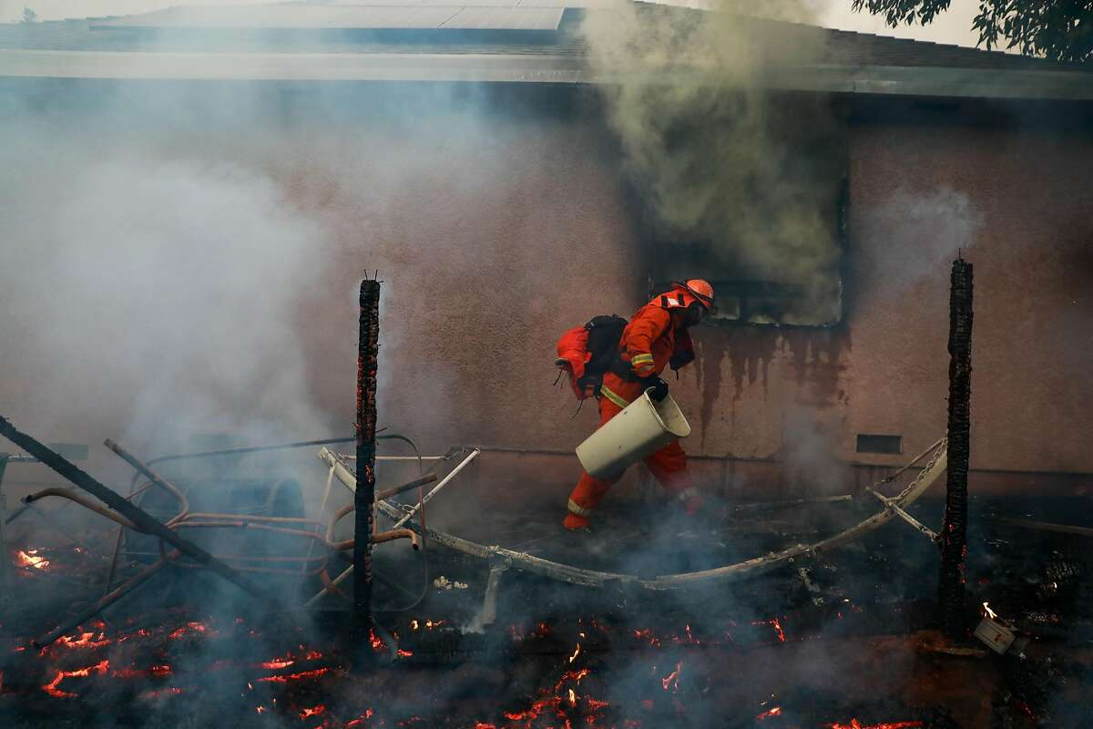 An inmate firefighter works to save a house off of Pentz Road during the Camp Fire in Paradise, California, on Thursday, Nov. 8, 2018.