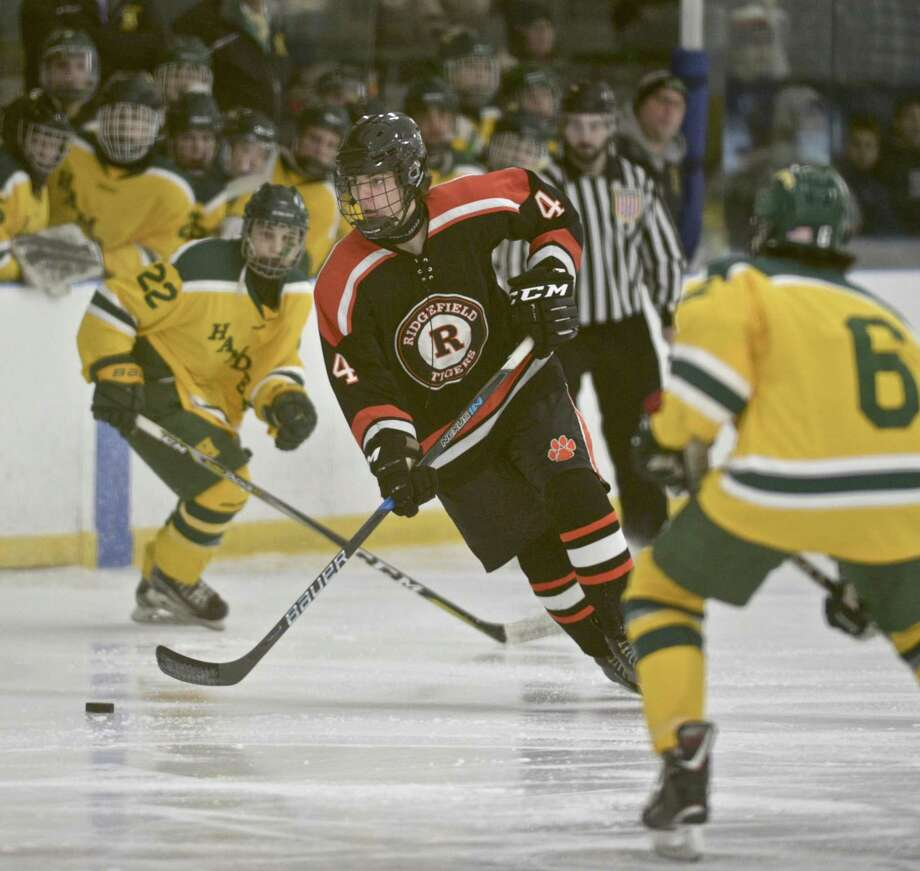 Ridgefield's Simon van Wees splits Hamden's Bryce Riccitelli, left, and Tyler Routh as he moves with the puck in Saturday's game. Photo: H John Voorhees III / Hearst Connecticut Media / The News-Times