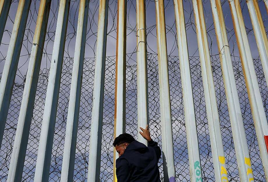 A man at the border wall in Tijuana, Mexico, this week. Photo: Gregory Bull / Associated Press