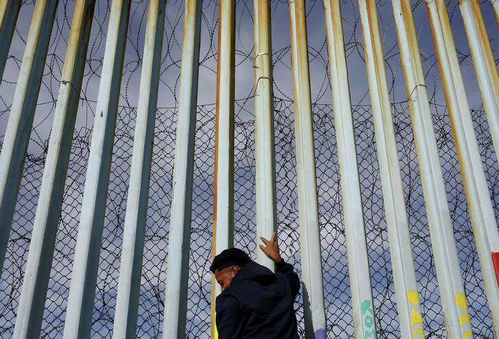A man holds on to the border wall along the beach, Tuesday, Jan. 8, 2019, in Tijuana, Mexico. As he was getting ready to make his case on prime-time TV Tuesday, President Donald Trump stressed humanitarian as well as security concerns at the U.S.-Mexico border to convince America he must get funding for his long-promised border wall before ending a partial government shutdown that has hundreds of thousands of federal workers facing missed paychecks.