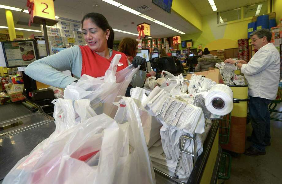 Cashier Beatriz Jimenez bags groceries at CTown on Tuesday in Norwalk. The Norwalk Common Council voted on Tuesday night to ban single-use plastic shopping bags, effective in six months. Photo: Erik Trautmann / Hearst Connecticut Media / Norwalk Hour