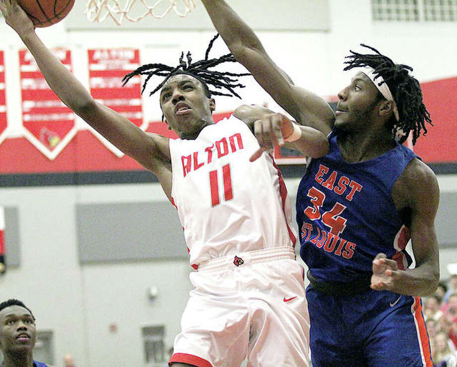Alton's Donovan Clay (left) is fouled by East St. Louis' Terrance Hargrove at the rim in the first half Tuesday night at Alton High in Godfrey. Clay made the basket and converted the three-point play in his 27-point outing in a Redbirds' loss. Photo: Greg Shashack | The Telegraph