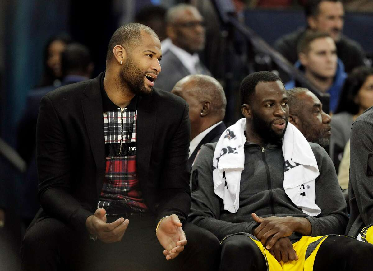 DeMarcus Cousins chats with Draymond Green (23) on the bench in the first half as the Golden State Warriors played the New York Knicks at Oracle Arena in Oakland, Calif., on Tuesday, January 8, 2019.