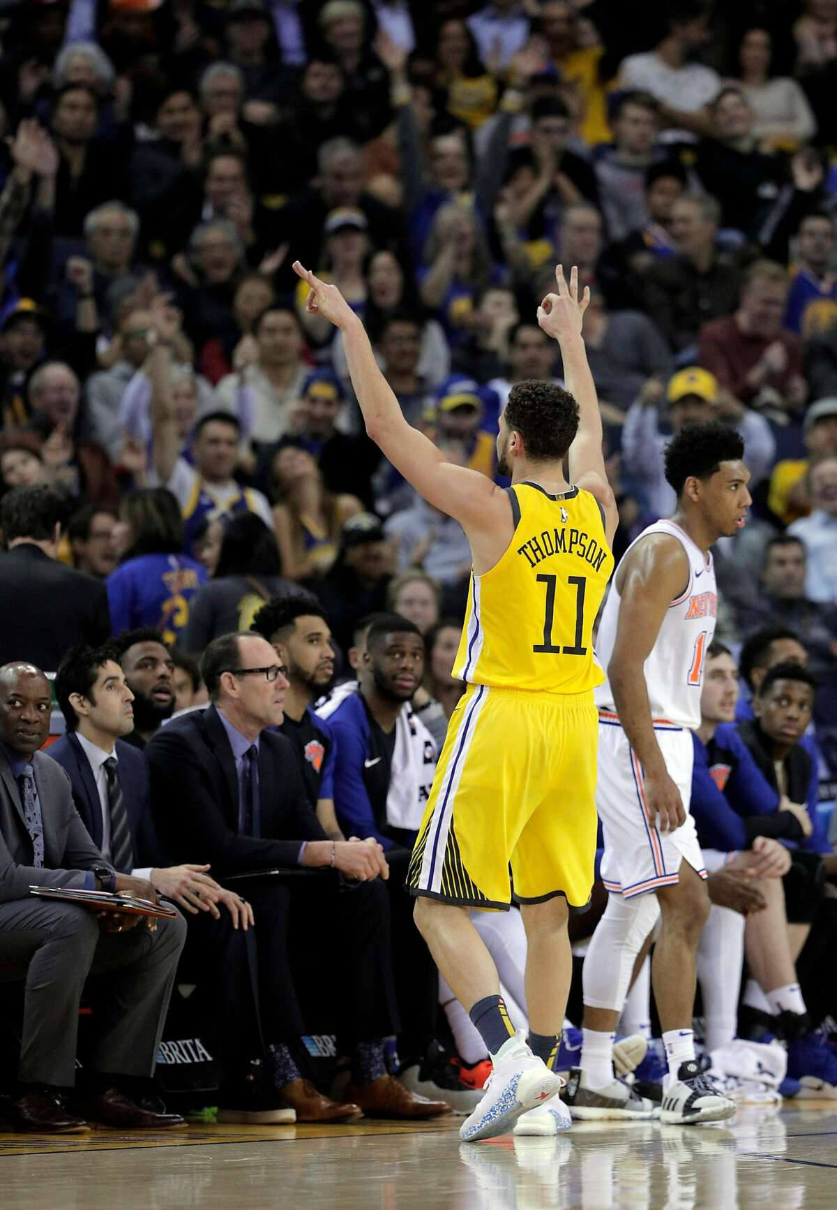 Klay Thompson (11) gestures to the crowd after hitting a three pointer late in the second half as the Golden State Warriors played the New York Knicks at Oracle Arena in Oakland, Calif., on Tuesday, January 8, 2019.