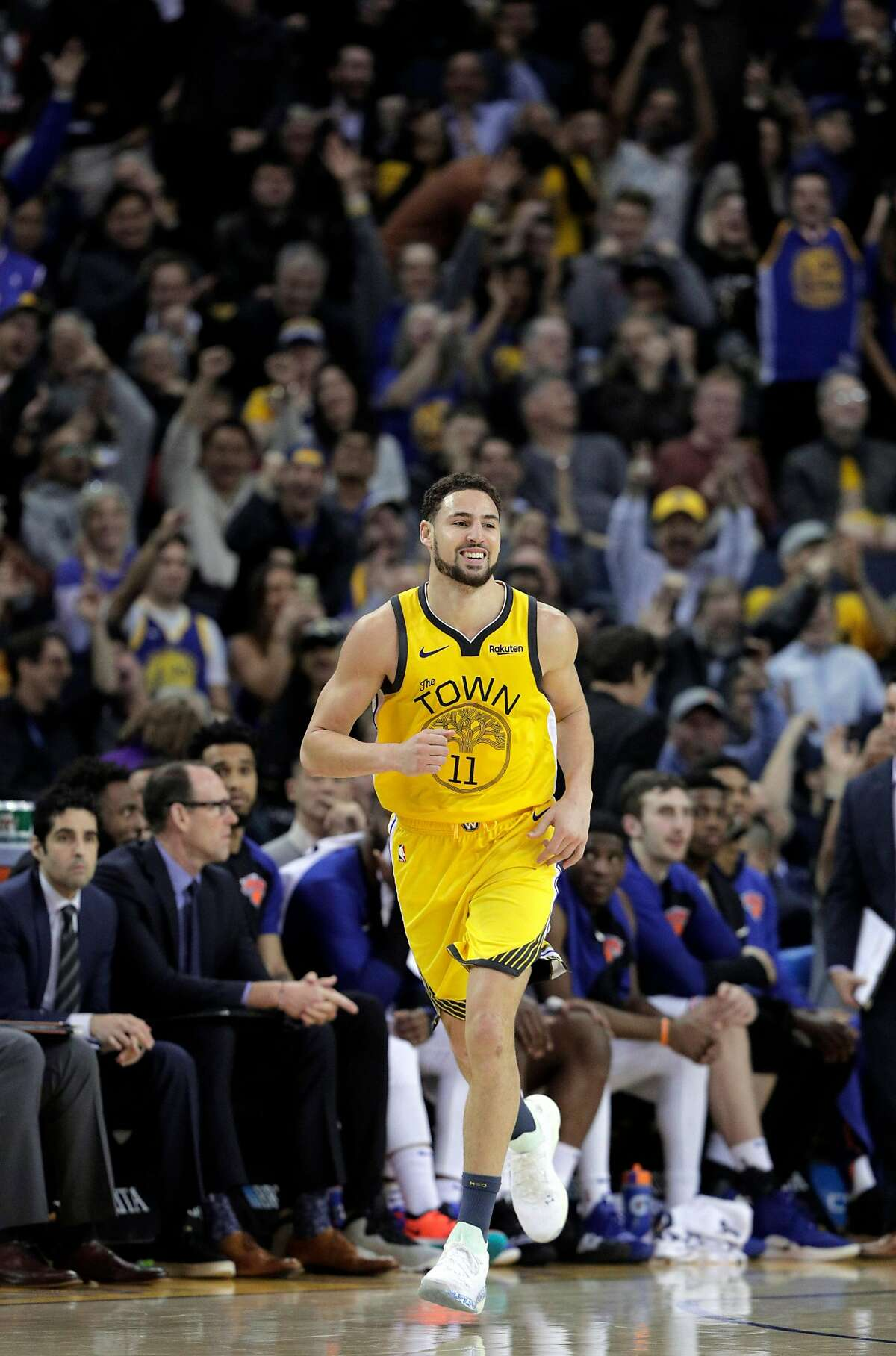 Klay Thompson (11) runs back up court with the fans cheering after hitting a three point shot late in the second half as the Golden State Warriors played the New York Knicks at Oracle Arena in Oakland, Calif., on Tuesday, January 8, 2019.