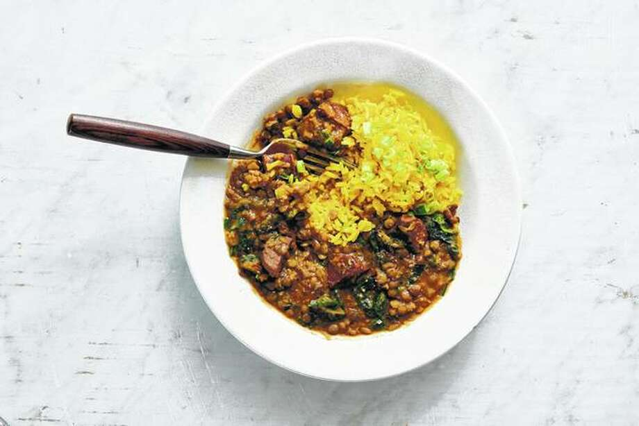 A stew of lentils, chorizo and greens served with yellow rice is hearty, filling and delicious no matter when you have it. Photo: David Malosh | The New York Times