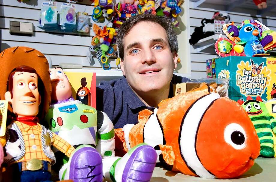 John Babina poses with some of the characters available in his toy store Polly Wolly Doodle at 607 Main Avenue in Norwalk Tuesday, July 20, 2010. This is his first brick and mortar venture after years of running toy-related internet businesses. Photo: Keelin Daly / Stamford Advocate