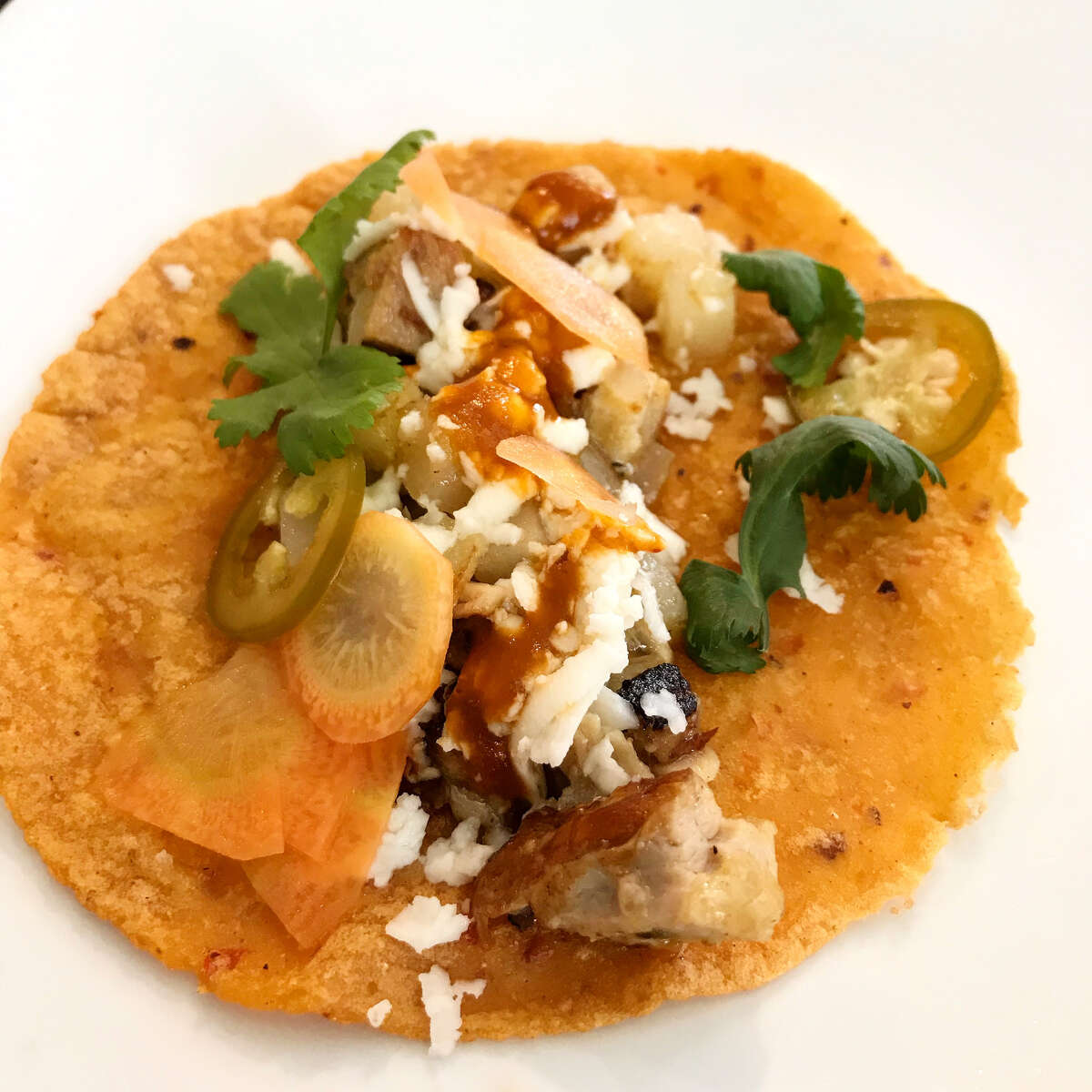 Crispy pork belly, poatoes and carrots on a chile de arbol corn tortilla from the taco pop-up dinners hosted by Cesar Cano.