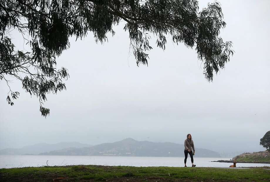 A woman walks on Albany Beach during a break between storms in Albany. Photo: Paul Chinn / The Chronicle