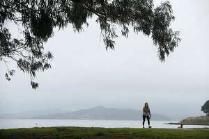 A woman walks on Albany Beach during a break between storms in Albany, Calif. on Wednesday, Jan. 9, 2019.