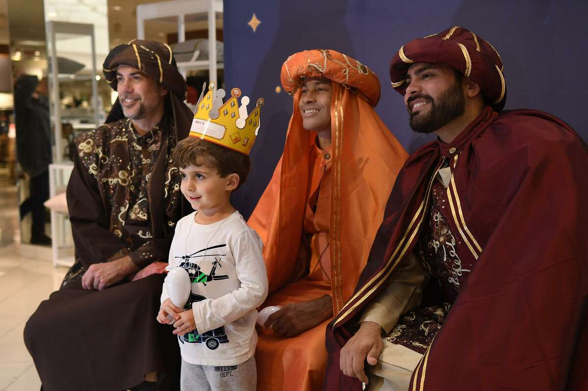 Lorenzo Iglesias, 4, poses for a photo with the Three Kings, including