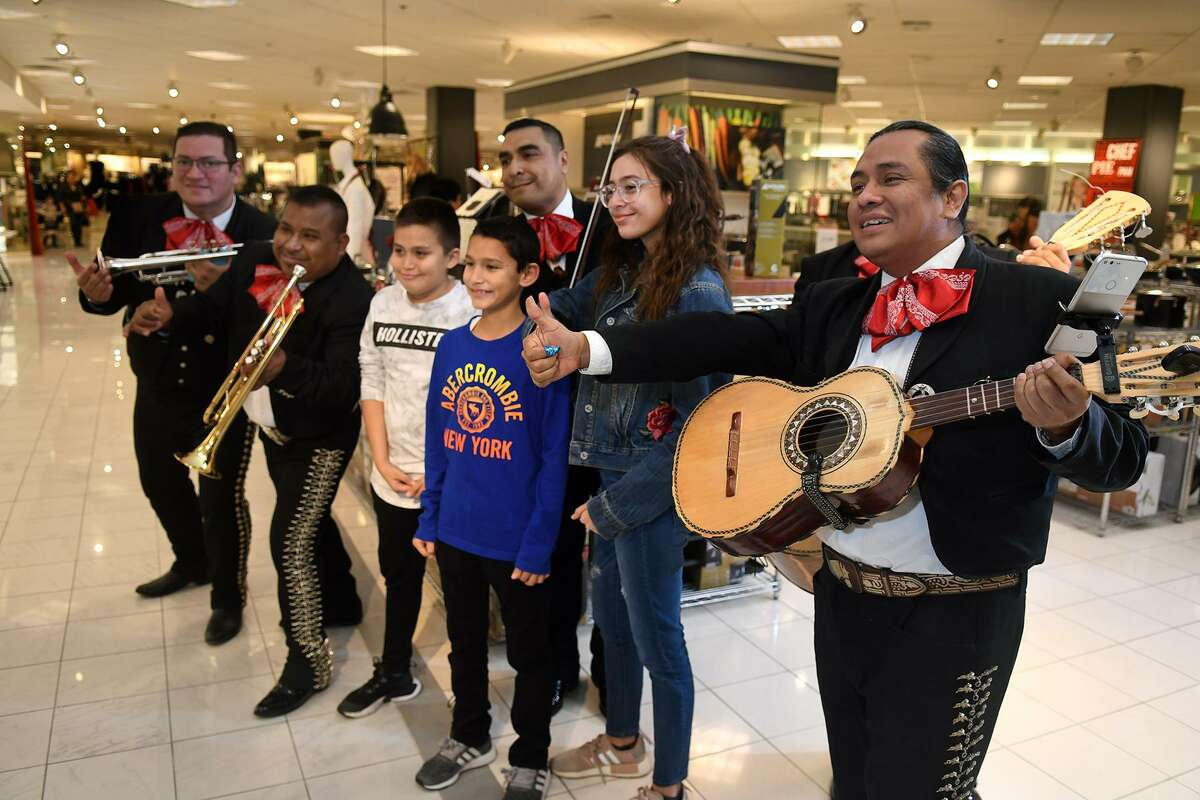 Pablo Solis, from right, and his fellow Mariachi CALMECAC falisciense members pose for a photo with Sara Castanon, 15, Cy Ranch High School sophomore, and her brothers David, 13, an Aragon Middle School 7th grader, and Samuel, 10, a Birks Elem. 5th grader, during their performance at the Macy's Three Kings Day celebration at Willowbrook Mall in Houston on Jan. 4, 2019.