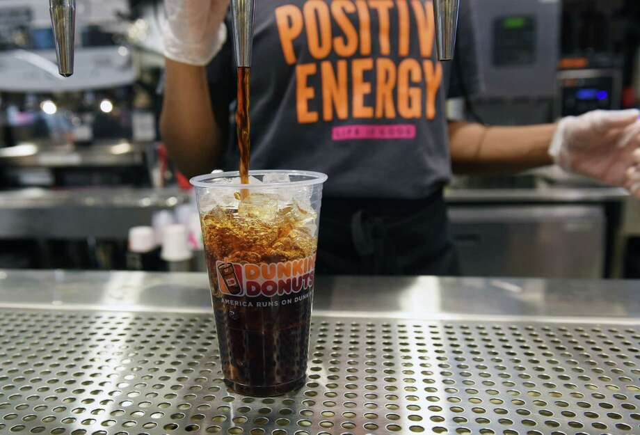 Shay Boyd uses the new Dunkin' tap system to pour a cup of iced coffee during the first day of the new Dunkin' restaurant Wednesday, Jan. 9, 2019 in Albany, N.Y. (Phoebe Sheehan/Times Union) Photo: Phoebe Sheehan, Albany Times Union