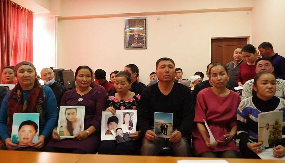 Relatives of people missing in China's far western region of Xinjiang hold up photos at an office of a Chinese Kazakh advocacy organization in Almaty, Kazakhstan. Photo: Dake Kang / Associated Press