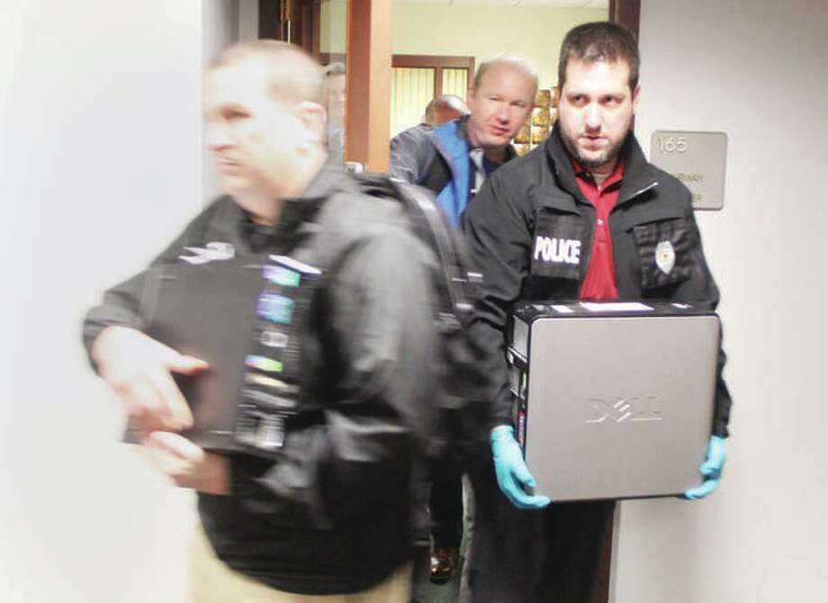 "Police officers remove items from the Madison County Board office after serving search warrants Jan. 10, 2018. The warrants were served by the ""Madison County Public Corruption Task Force."" There have been no charges filed, but the investigation is ""ongoing"" according to a spokesperson from the Illinois Attorney General's Office, which is handling the case. Photo: Scott Cousins 