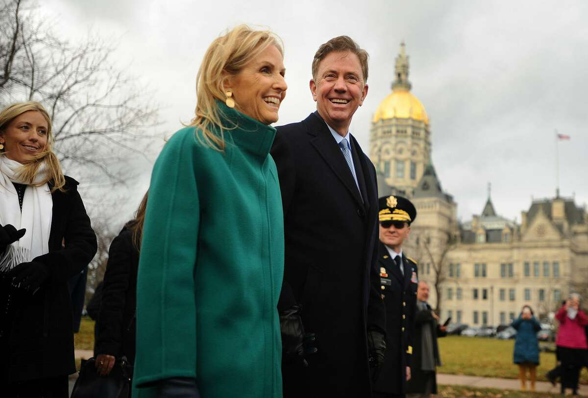 Flanked by daughter Lindsay, left, and wife Annie, newly sworn in Governor Ned Lamont marches in a parade past the Capitol in Hartford, Conn. on Wednesday, January 9, 2019.