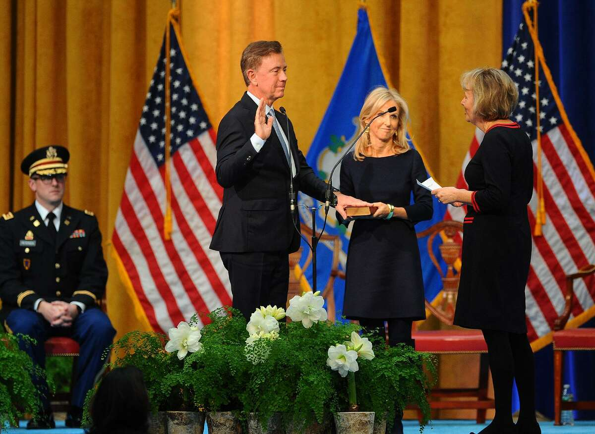 The Bible held by his wife Annie, Governor Ned Lamont is sworn in by retired Chief Justice marches in a parade past the Capitol in Hartford, Conn. on Wednesday, January 9, 2019.Chase T. Rogers at the William A. O'Neill Armory in Hartford, Conn. on Wednesday, January 09, 2019.