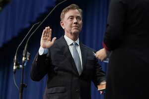 Connecticut Gov. Ned Lamont takes the oath of office administered by former Chief Justice Chase T. Rogers, Wednesday, Jan. 9, 2019, inside the William A. O'Neill Armory in Hartford Conn. (AP Photo/Jessica Hill, Pool)