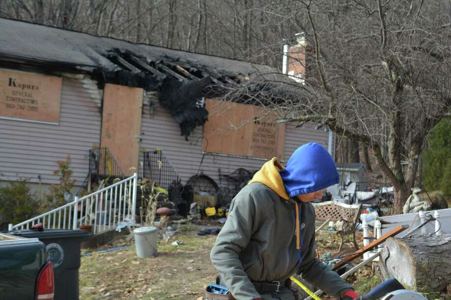 A worker prepares plywood to cover the windows of the fire-damaged house at 37 Stoneridge Dr. on Jan. 4. Photo: Leslie Hutchison / Hearst Connecticut Media /
