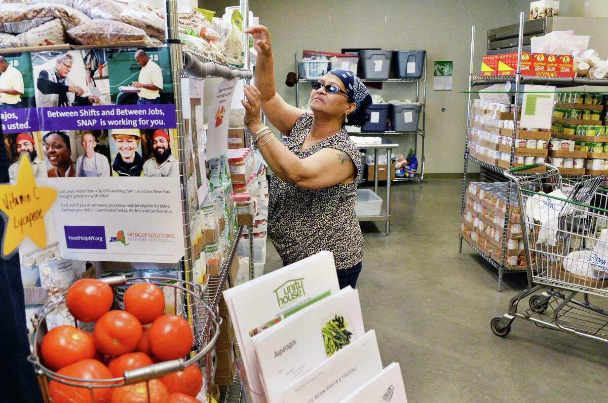 Volunteer Elba Pacheco stocks shelves at the food pantry in Unity House of Troy Inc. Friday June 2, 2017 in Troy, NY. (John Carl D'Annibale / Times Union)