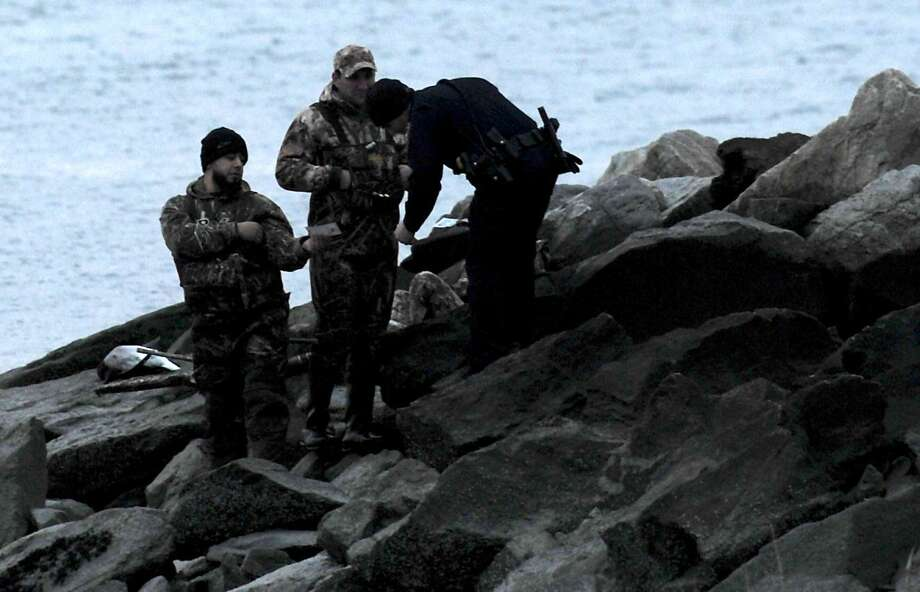 Norwalk police check the hunting lincenses of duck hunters in November at Calf Pasture Beach in Norwalk. Photo: Erik Trautmann / Hearst Connecticut Media / Norwalk Hour