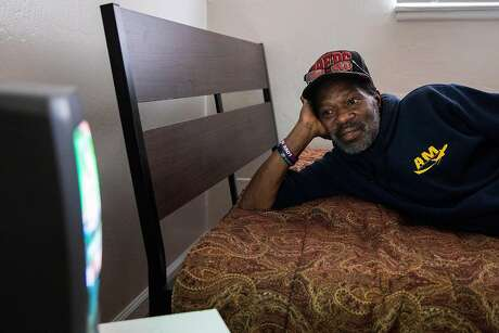 Marcus Emery formerly homeless, watches the Game Show Network from his own bed on his own TV in the bedroom of his new East Oakland apartment. Photo: Jessica Christian / The Chronicle