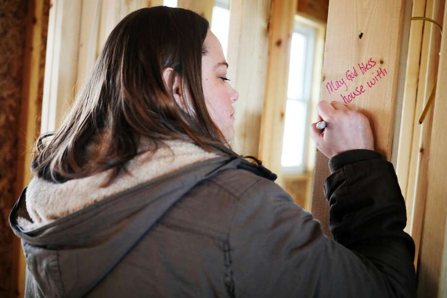Heather Patterson writes a message on a piece of wood during a framing party to celebrate the progress on a home being built for Midland's Open Door's Building for Change fundraising initiative on Wednesday, Jan. 9, 2019 in Midland. (Katy Kildee/kkildee@mdn.net) Photo: (Katy Kildee/kkildee@mdn.net)