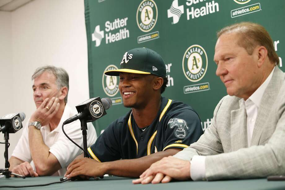 In this file photo, Executive Vice President of Baseball Operations Billy Beane of the Oakland Athletics, first round draft pick Kyler Murray and Agent Scott Boras talk during a press conference after Murray signed his contact at the Oakland Alameda Coliseum on June 15, 2018 in Oakland, California. (Photo by Michael Zagaris/Oakland Athletics/Getty Images) Photo: Michael Zagaris / Getty Images