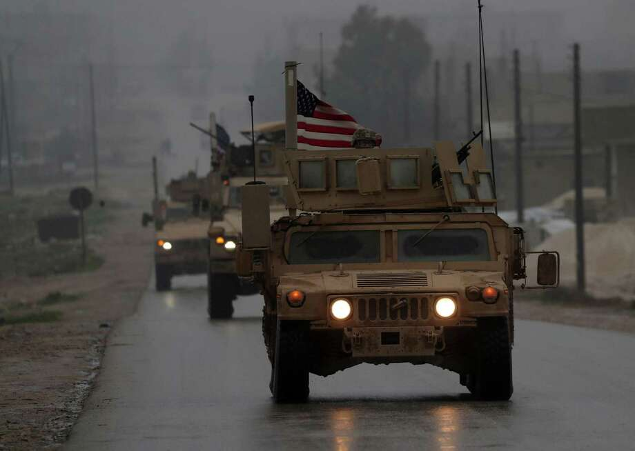 A line of US military vehicles in Syria's northern city of Manbij last month. A reader implores Rep. Will Hurd and other members of Congress to dissuade the president from withdrawing U.S. troops from Syria. Photo: DELIL SOULEIMAN /AFP /Getty Images / AFP or licensors