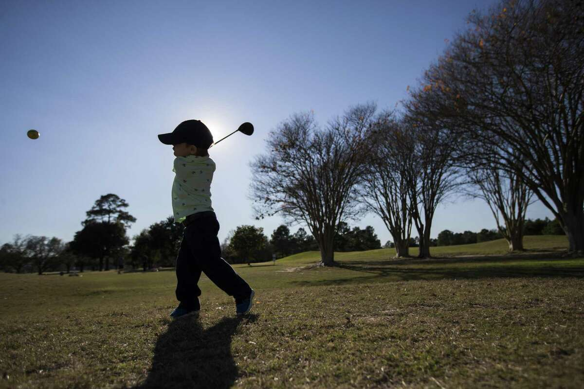 The silhouette of Landis Roccaforte, 3, is seen as he practices his long-distance shot on Wednesday at Memorial Park Golf Course, Jan. 9, 2019, in Houston.
