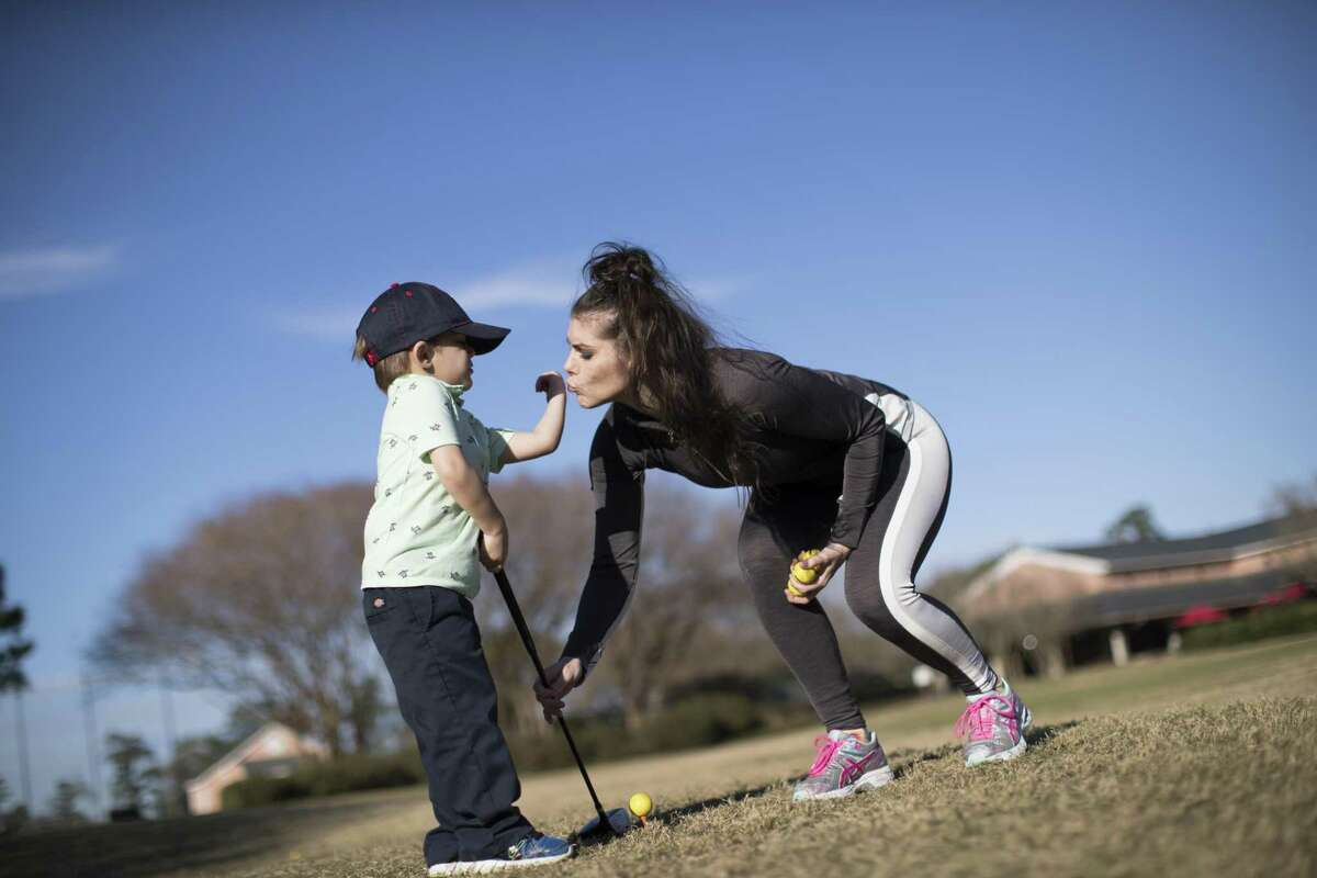 Mary Verbeck kisses the hand of her son Landis Roccaforte, 3, after the young golfer complaint of pain on his hand after a practice session at the on Wednesday at Memorial Park Golf Course, Jan. 9, 2019, in Houston.